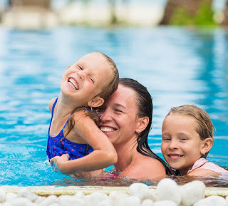 Image of a happy mother and her son holding up a little girl in the pool. Swimming Lesson ideas often change lesson plans.