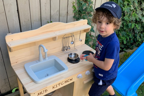 boy pretending to work at mcdonalds in mud kitchen outside