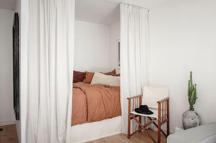 Dormitorio en el salón con cortinas y ropa de cama en color caldera.