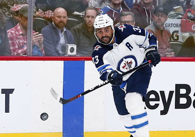 Dustin Byfuglien passing ice hockey ball