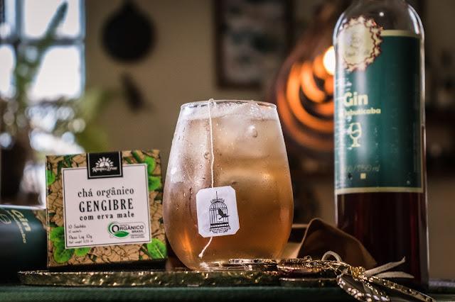 Drink Gin Tônica com garrafa e gin e caixa de chá ao lado