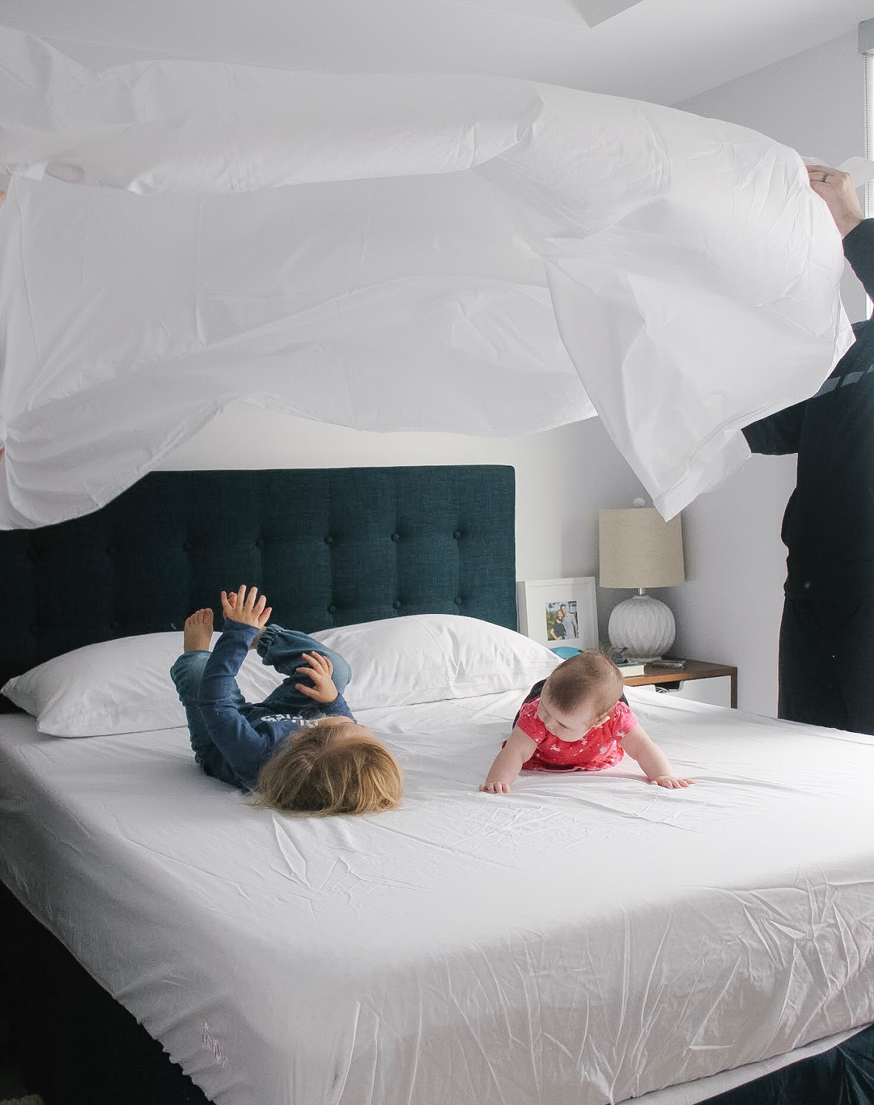 making the bed with toddler and baby on Endy mattress