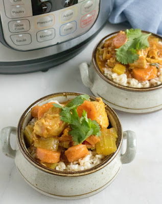 chicken and vegetable curry served over rice in front of instant pot