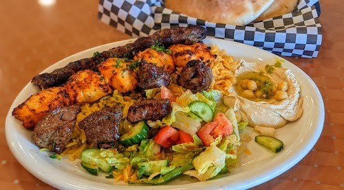 Mixed grill plate with three kababs, hummus, and salad.