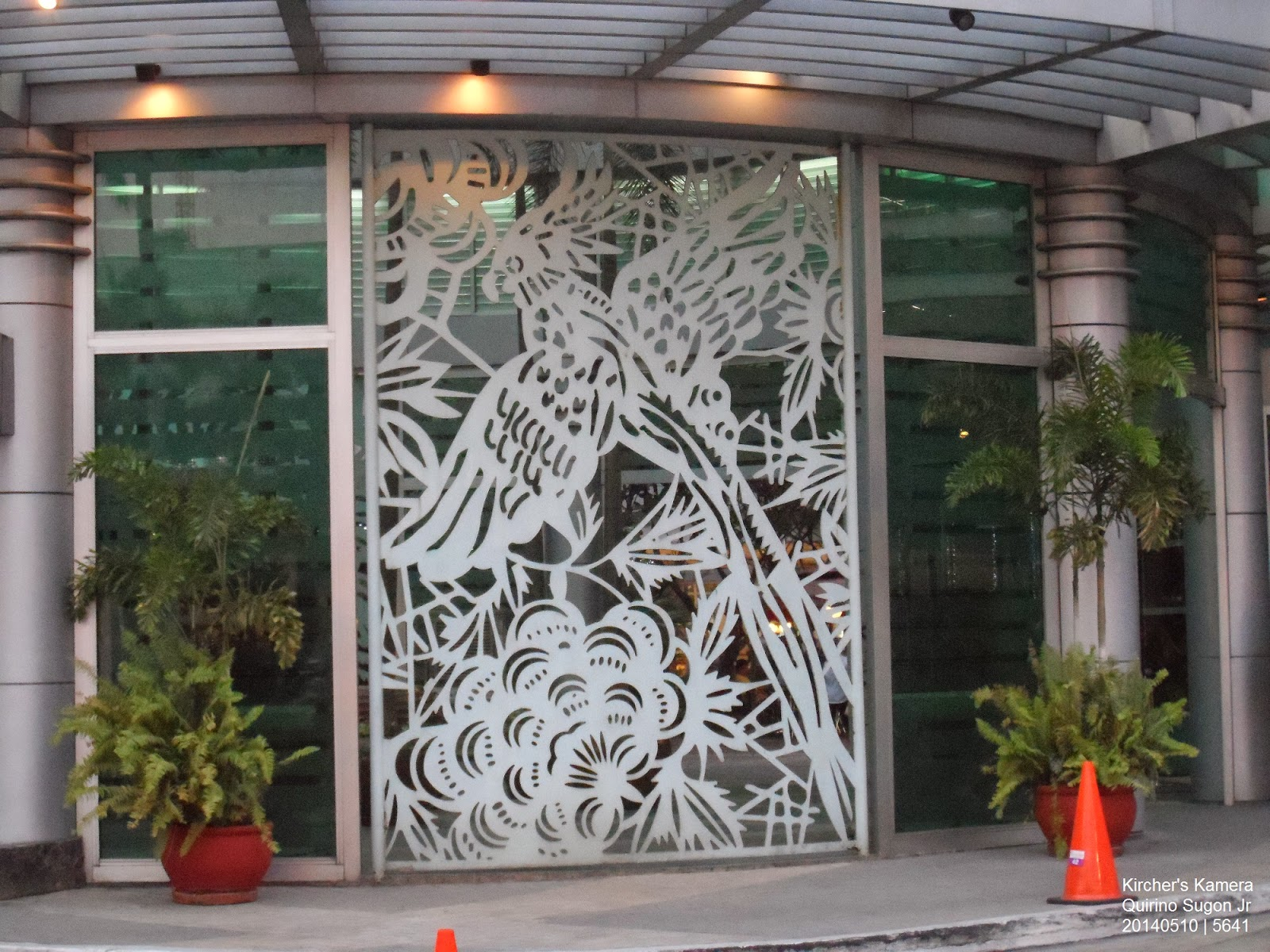 The white bird design at the main entrance of Gateway Mall. The bird looks like a parrot.  Below the bird is probably a cluster of flowers.  Two plants flank the bird art near the two polished steel columns.