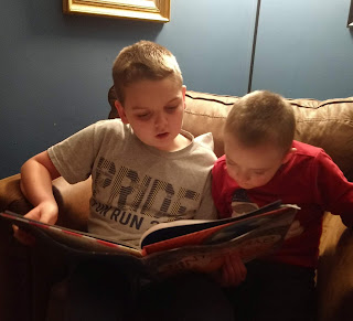 a boy in a gray t-shirt reads to a smaller boy in a red sweatshirt while both sit in a brown chair.