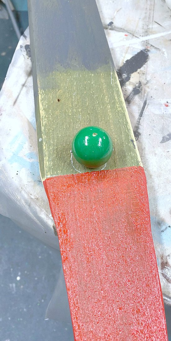 painted board with a wooden ball for a nose