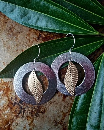 Metallic silver and gold tone earrings featuring a leaf shape overlapping a doughnut shape.