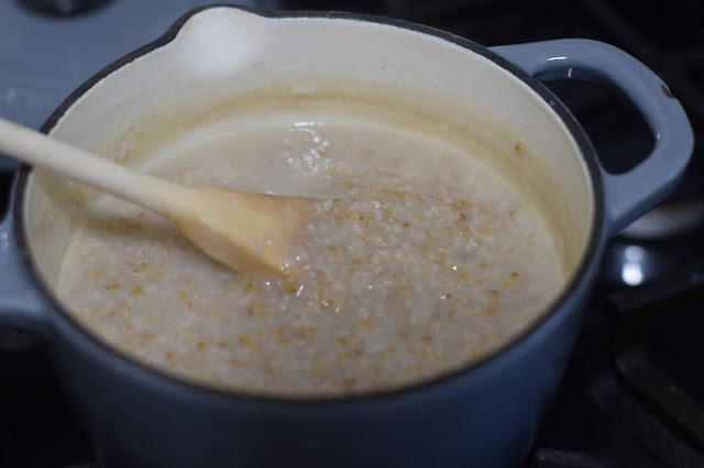 The fully cooked steep cooked oats in a pot with a wooden spoon in it.  h a wodden spoon in it.