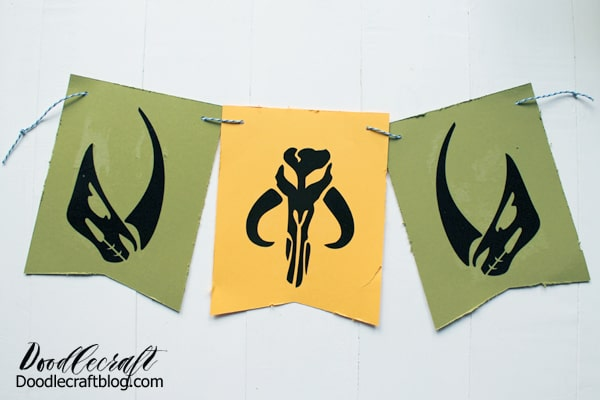 Mudhorn silhouette and Mandalorian symbol cut out of black vinyl and adhered to cardstock bunting for a mandalorian themed birthday party.