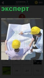 двое рабочих в касках в качестве эксперта рассматривают схему