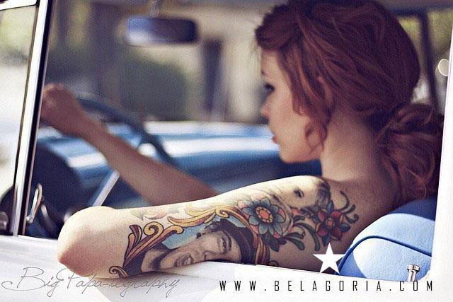 Mujer en su auto lleva tatuajes en el brazo