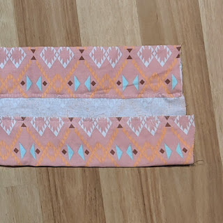 A rectangle of pink fabric has been folded on each long side with the raw edges sewn with whip stitch and running back stitch.