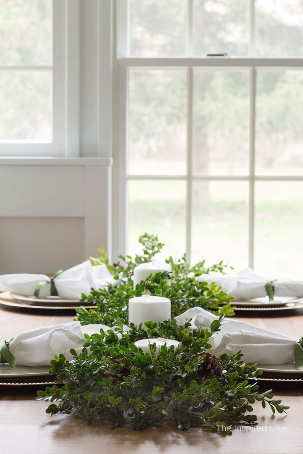 How to decorate a table for Christmas on a budget! Beautiful farmhouse winter tablescape using a boxwood runner as a DIY centerpiece.
