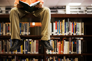 young man sitting on top of bookshelves reading a book