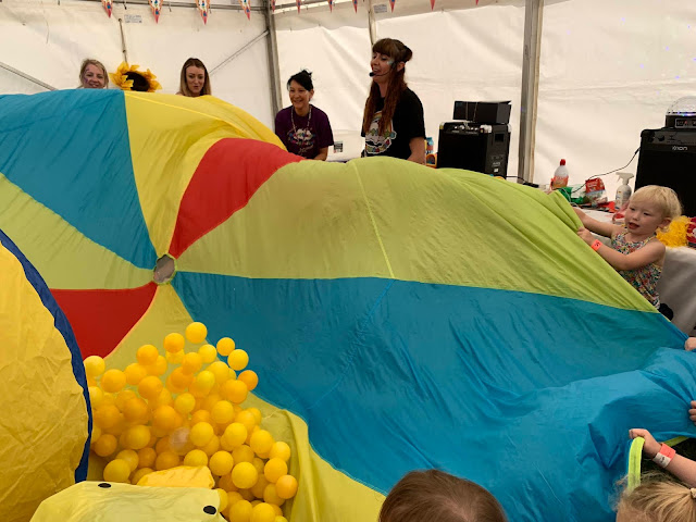 A parachute being waved up and down with yellow plastic balls in to represent popcorn in the Hartbeeps 3 foot people festival session
