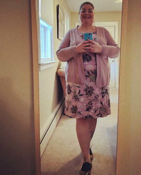 image of me standing in a full-length mirror, wearing a purple flowered dress and a lilac cardigan with brown and navy oxford shoes, with my contacts in and hair pulled back in a ponytail