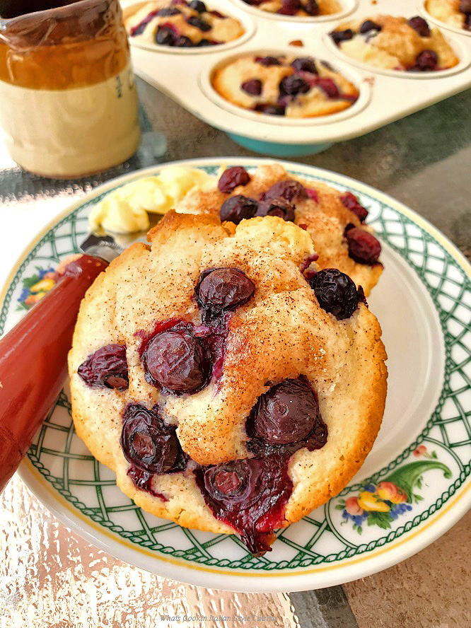 Blueberry Sour Cream Muffins with a slab of butter on a fruit lenox china plate with the rest of the baked muffins in a tin in the background along with a brown 1/2 cup pitcher