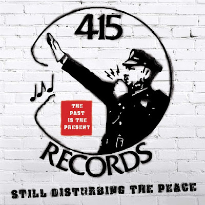 The album cover features a white brick wall with the spray-painted image of a policeman holding up his arm and blowing a whistle.