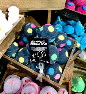 A group of black spherical bath bombs with colourful circular spots of colour on the side in a large light brown rectangular box on a bright background