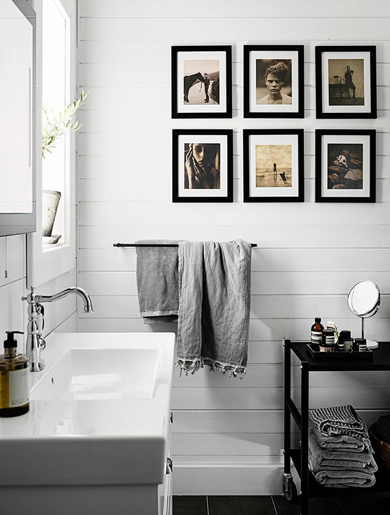 Bathroom with black and white framed photos on the wall. Photo by Kristofer Johnsson, styling by Pella Hedeby via Elle Decoration