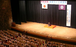講演会講師・三遊亭楽春の落語で笑う健康講演会の風景。