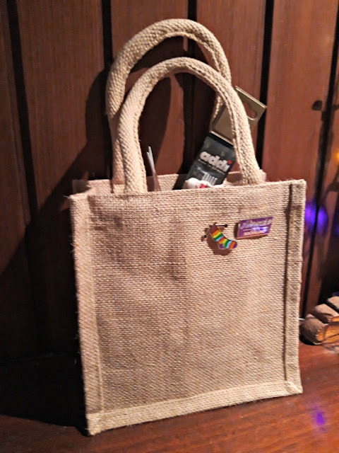 A photo of a small jute sandwich bag used as a knitting project bag.