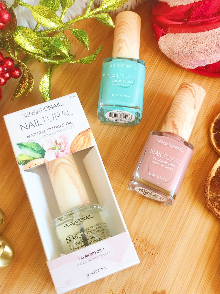 flatlay - sensationail pink and blue nail polishes and natural cuticle oil on heart chopping board