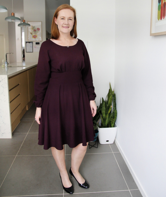 a photo of a white woman posing in a maroon dress