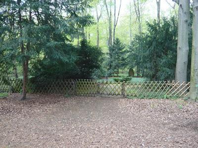 Ein kleiner Friedhof, umgeben von einem Jägerzaun. Im Hintergrund sind zwei Gedenksteine zu erkennen