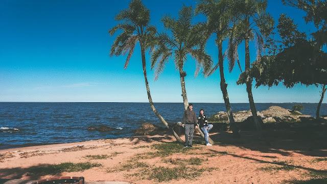 Casal encostado em árvores, na beira da praia