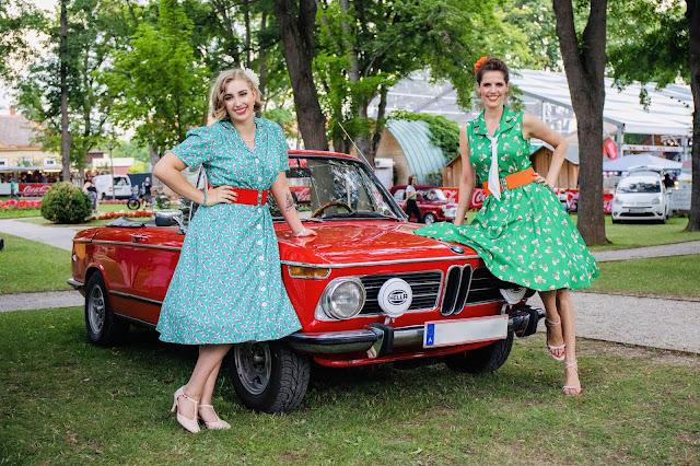 Angelika Buschka Miss A.B. West und Gudrun Blümel cooking fairy in kleidern von boutique new vintage an einem roten oldtimer lehnend bei rocknroll im kurpark Bad Sauerbrunn