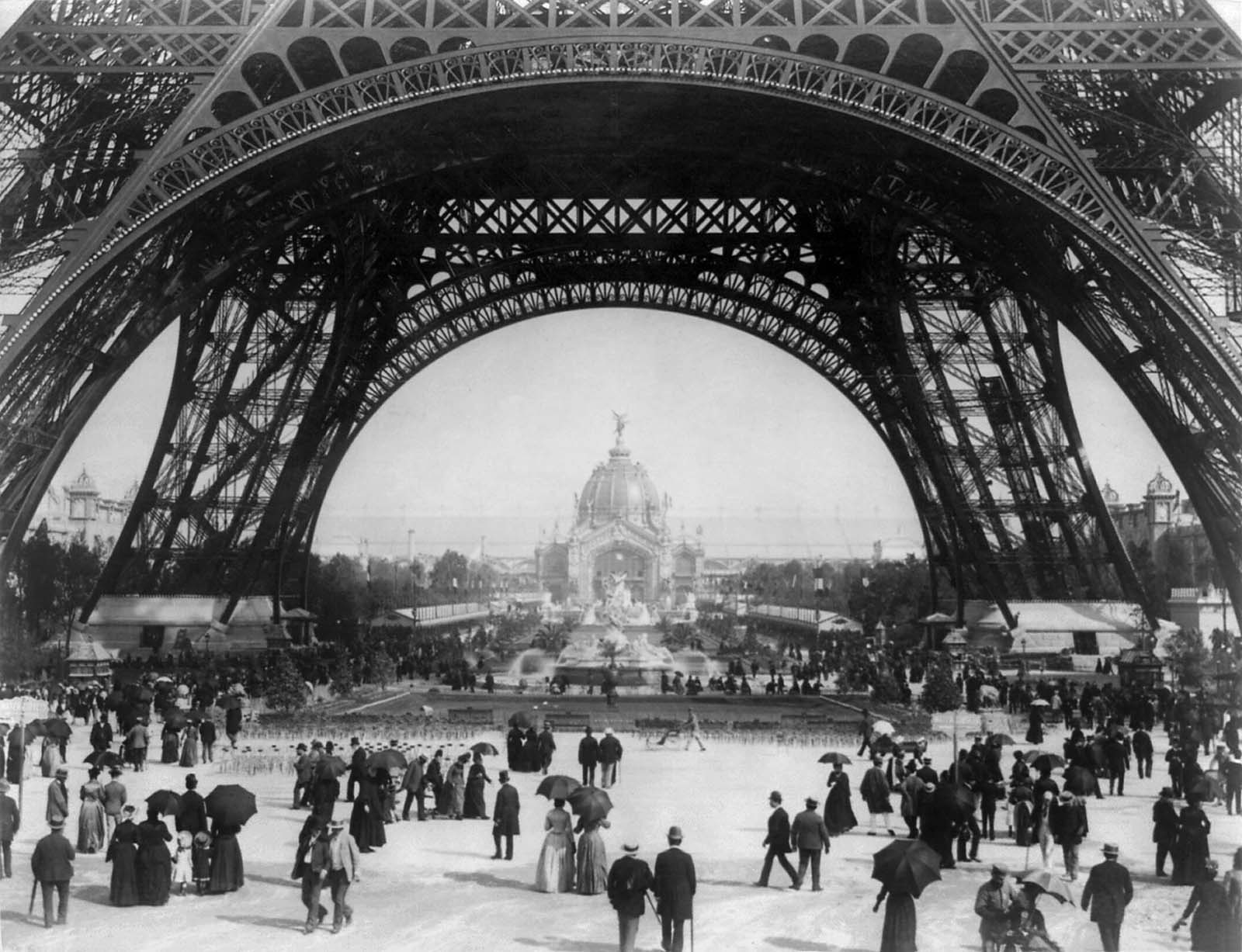Paris Exposition, view from ground level of the Eiffel tower with Parisians promenading, 1889.