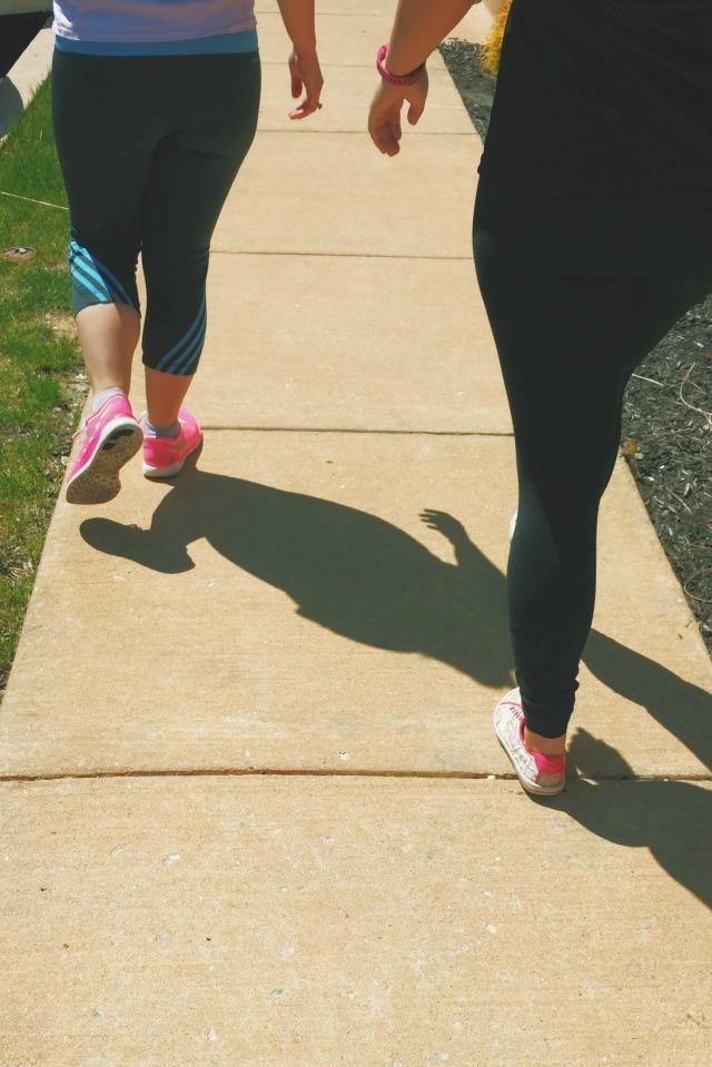 Girls walking on a sidewalk wearing leggings and sneakers.