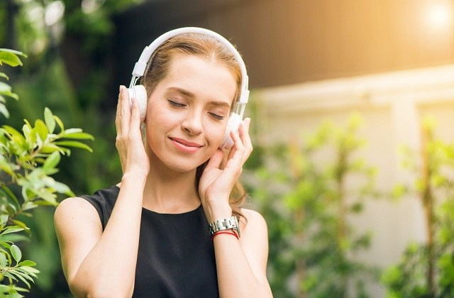 woman in black shirt with white headphones listening outdoors