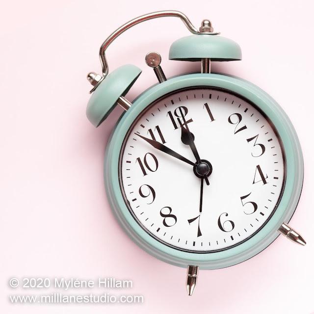 Retro green alarm clock on pastel pink background