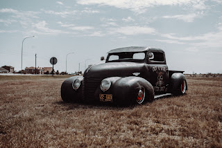 Black rat rod parked in the middle of brown grass field