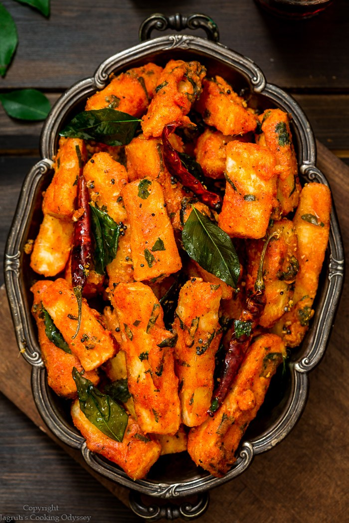 Mogo chips 65 served in a oval tray topped with fried curry leaves and red chillies.