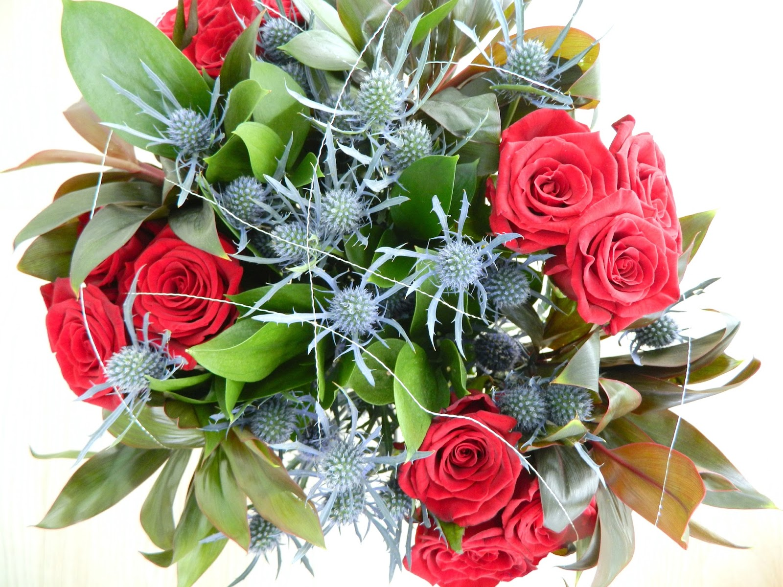 The Grandeur Bouquet From Their Luxury Range Features Stunning Avalanche  Red Roses, Complimented With Foliage Encased With Golden Orbits.