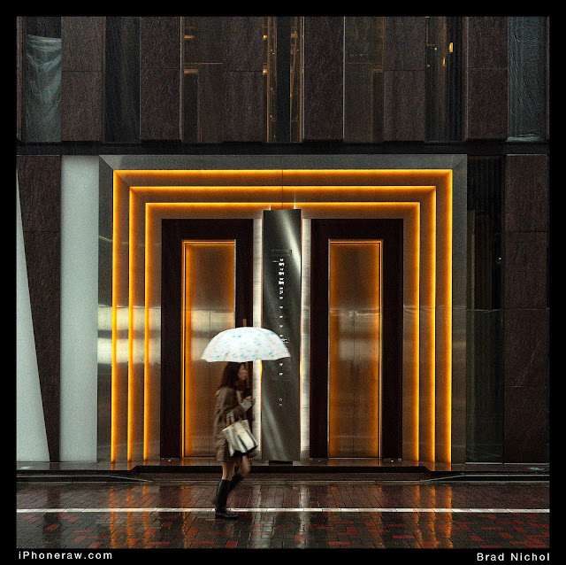 Ginza Laneway Japan with teeming rain and lady with umbrella during typhoon.