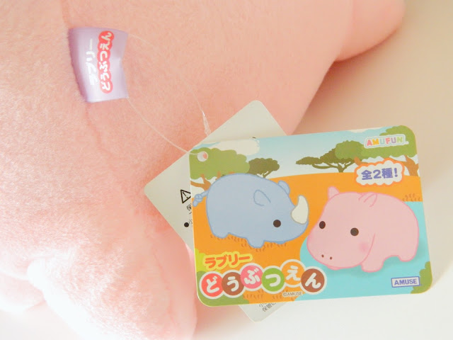 A photo of a label for a pink hippo plush toy from Japan. There is an illustration of a hippo and a rhino.