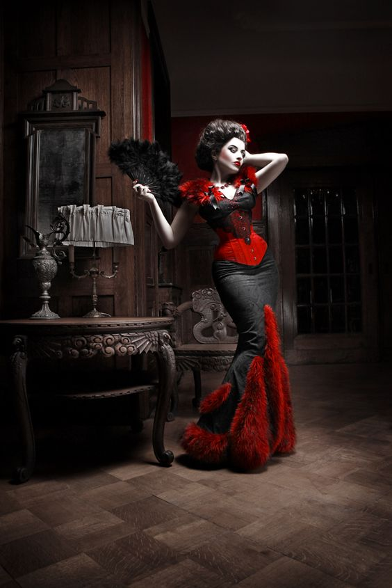 Woman dressed in red and black neo-victorian gown with fishtail skirt and red fur accents. Black and red lace underbust corset. Black fur folding fan. Victorian inspired ball gown.