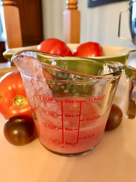 Glass measuring cup showing a half cup of tomato puree.
