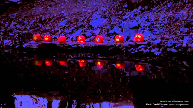 Jack-o-Lanterns lined up on the shore of the Provo River
