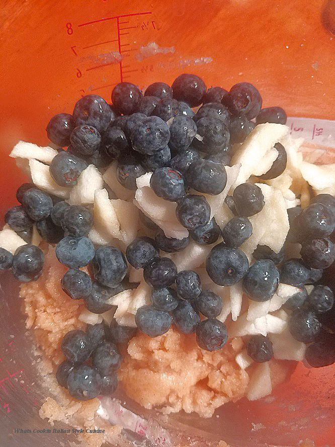 Blueberries and sliced chopped apples being added to the muffin batter