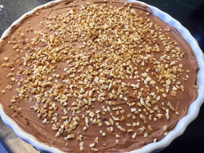 Whole cheesecake in a white dish sprinkled with hazelnuts