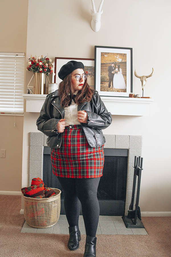 A plus size outfit consisting of a black beret, black faux leather moto jacket, white Peter Pan collar blouse, classic red tartan plaid mini skirt, black tight and black heeled chelsea boots