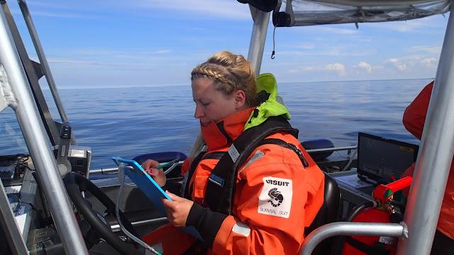 Nainen pelastautumispuvussa kirjoittaa kirjoitusalustalle veneessä tyynellä merellä
