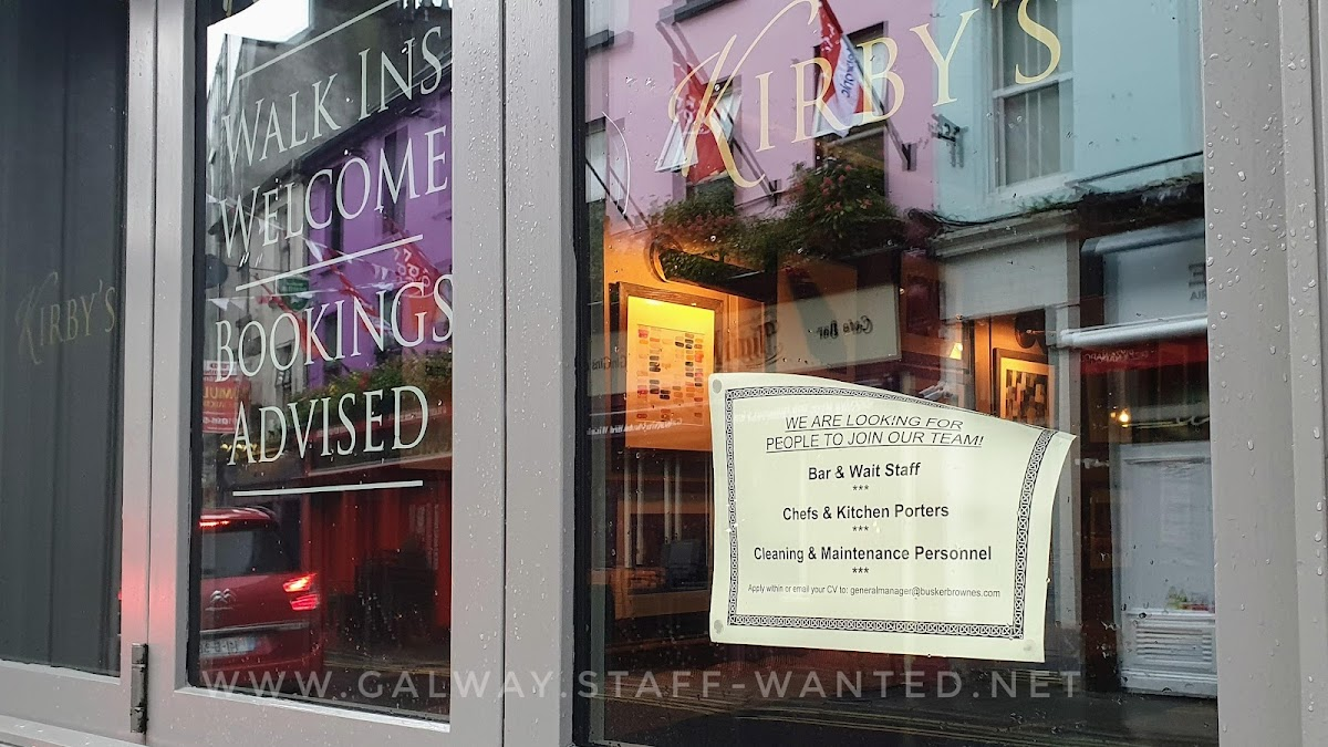 Kirby's Galway - walk-ins welcome, bookings advised - highly polished restaurant windows reflecting lights from Nora's Gin Bar across the street - and a job advert, looking for people to work in all parts of their business