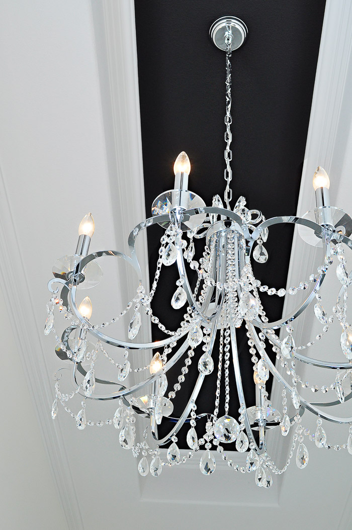 A large foyer chandelier in chrome with swarovski crystals hung from a black tray ceiling.